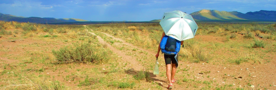 When it's hot and dry like New Mexico, you'll need to carry extra water, like I'm doing here. Since you sweat less with an umbrella, you'll need less water than without an umbrella