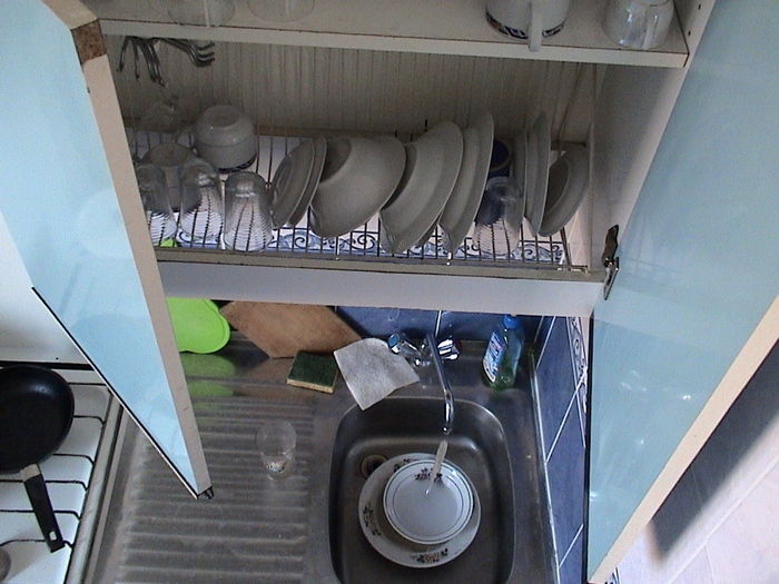 After washing dishes in my apartment in Minsk, Belarus, I would immediately put the wet dishes on the dish rack that is in the cabinet. This simple solution saves you a step when hand-washing dishes.
